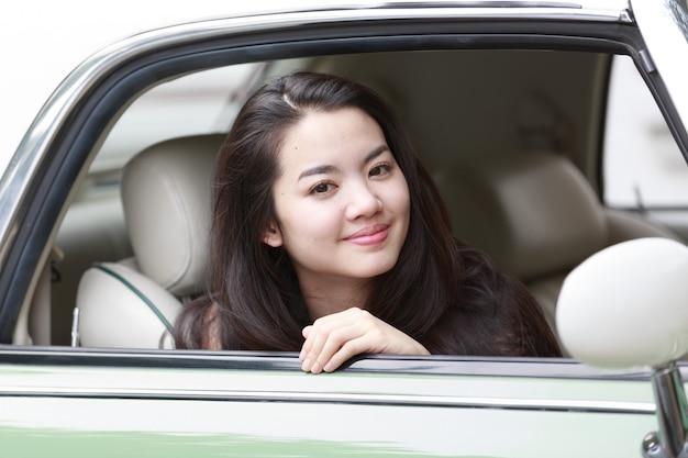 Junge asiatische dame in einem weinleseauto
