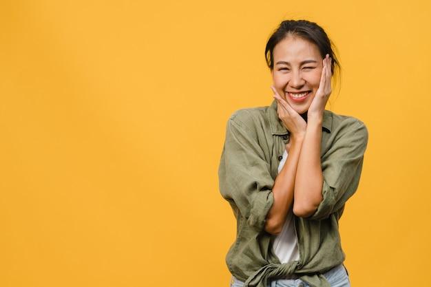 Junge asiatische dame mit positivem ausdruck, breites lächeln, gekleidet in freizeitkleidung über gelber wand. glückliche entzückende frohe frau freut sich über erfolg. gesichtsausdruck konzept.