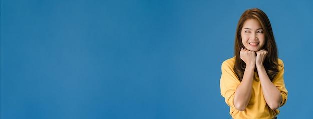 Junge asiatische dame mit positivem ausdruck, lächeln breit, gekleidet in freizeitkleidung lokalisiert auf blauem hintergrund. glückliche entzückende frohe frau freut sich über erfolg. panorama-bannerhintergrund mit kopierraum