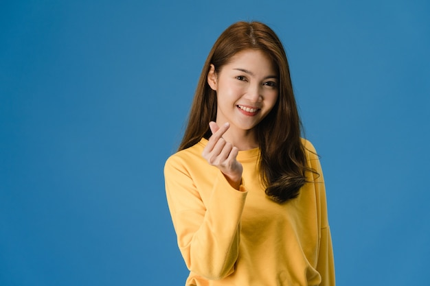 Junge asiatische dame mit positivem ausdruck, zeigt handgeste in herzform, gekleidet in freizeitkleidung und blick auf kamera lokalisiert auf blauem hintergrund. glückliche entzückende frohe frau freut sich über erfolg.