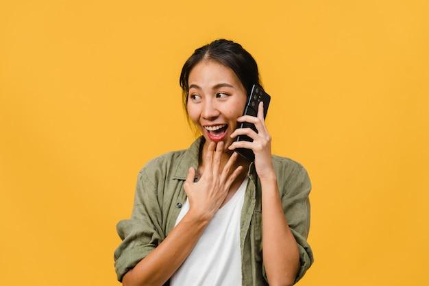 Junge asiatische dame spricht per telefon mit positivem ausdruck, lächelt breit, in freizeitkleidung gekleidet, fühlt sich glücklich und steht isoliert auf gelber wand. glückliche entzückende frohe frau freut sich über erfolg.