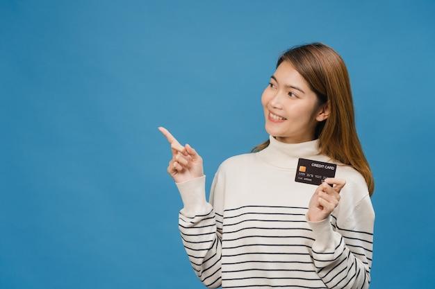Junge asiatische dame zeigt kreditkarte mit positivem ausdruck, lächelt breit, gekleidet in freizeitkleidung, fühlt sich glücklich und steht isoliert auf blauer wand