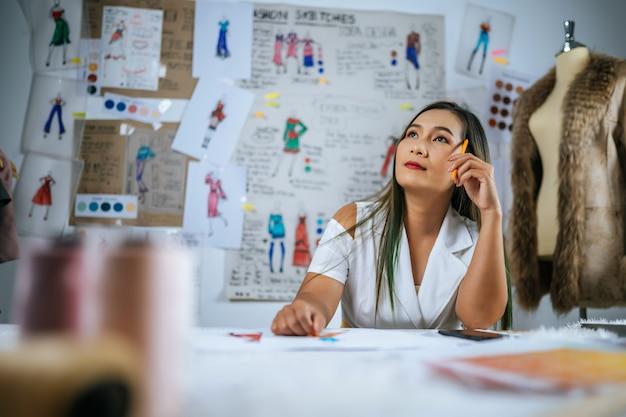 Junge asiatische designer kreieren mit ideen neue modetrends. schöner mantel in schaufensterpuppe und kleiderskizze an bord