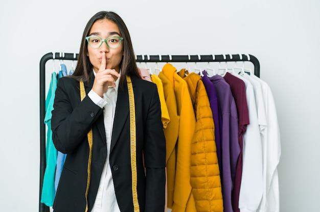 Junge asiatische designerfrau, die ein geheimnis hält oder um stille bittet.