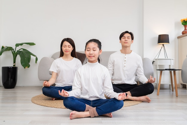 Junge asiatische familie, die übung zu hause zusammen macht