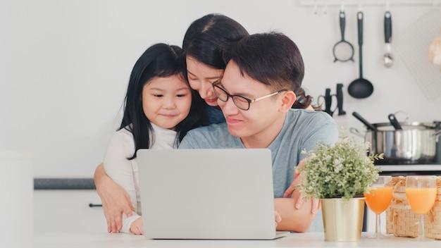 Junge asiatische familie genießen, laptop zusammen zu hause zu verwenden. junge umarmung des ehemanns, der frau und der tochter des lebensstils und spielen nach dem frühstück in der modernen küche am haus morgens.