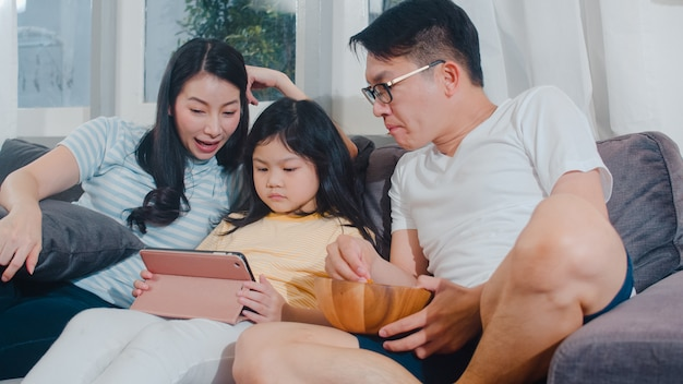 Junge asiatische familie und tochter glücklich, tablette zu hause verwendend. japanische mutter, vater entspannen sich mit dem aufpassenden film des kleinen mädchens, der auf sofa im wohnzimmer liegt. lustiges elternteil und reizendes kind haben spaß.