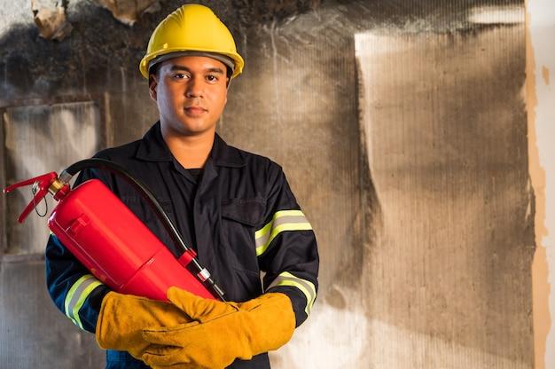 Junge asiatische feuerwehrleute, feuerwehrleute verwenden feuerlöscher, die im gebäude brennen.