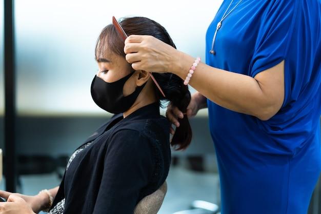 Junge asiatische frau am friseursalon, die chirurgische schützende gesichtsmaske trägt. neues normales und soziales distanzierungskonzept