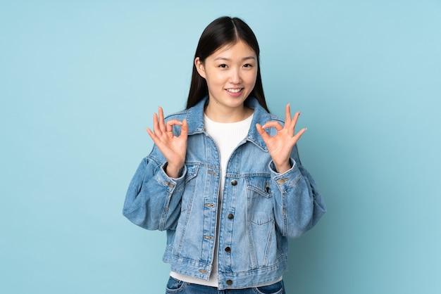 Junge asiatische frau an der wand, die ok zeichen mit zwei händen zeigt