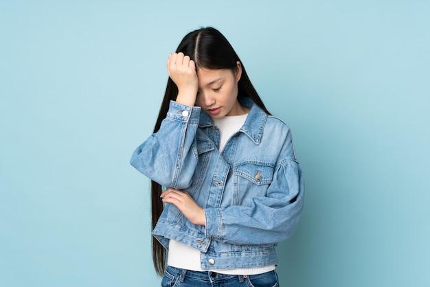 Junge asiatische frau an der wand mit kopfschmerzen