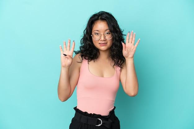 Junge asiatische frau auf blauem hintergrund isoliert, die neun mit den fingern zählt
