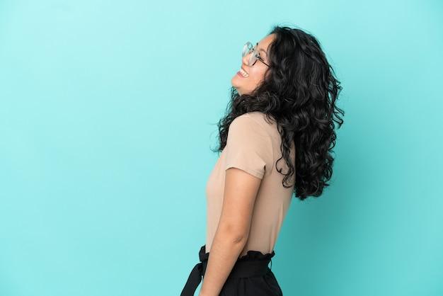 Junge asiatische frau auf blauem hintergrund isoliert lachend in seitenlage