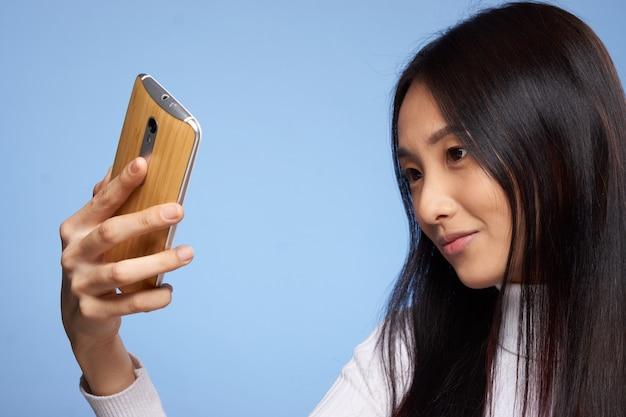 Junge asiatische frau auf einem blauen hintergrund, der aufwirft