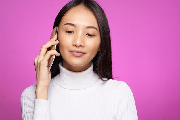 Junge asiatische frau auf einem lila hintergrund, der aufwirft