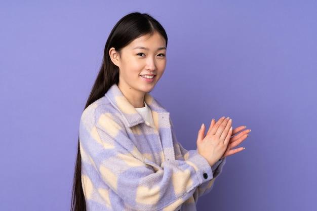 Junge asiatische frau auf lila wand applaudiert