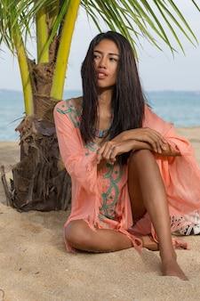 Junge asiatische frau auf palme. perfekte haut. blick auf den ozean. sonnenuntergang.