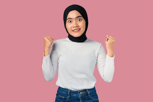 Junge asiatische frau aufgeregt auf rosa hintergrund