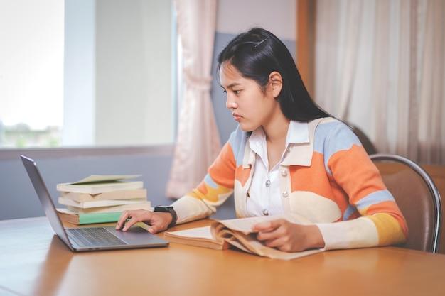 Junge asiatische frau college-student in studentenuniform studieren, ein buch, einen laptop in der universitäts- oder hochschulbibliothek lesen. jugendstudentin und nachhilfeunterricht mit einem technologischen lernkonzept