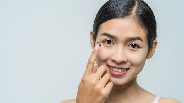 Junge asiatische frau der nahaufnahme, die kontaktlinse trägt, kamera betrachten.