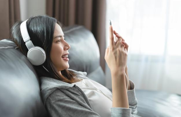 Junge asiatische frau des glücklichen lächelns, das musik von weißen kopfhörern hört und smartphone zu hause verwendet.