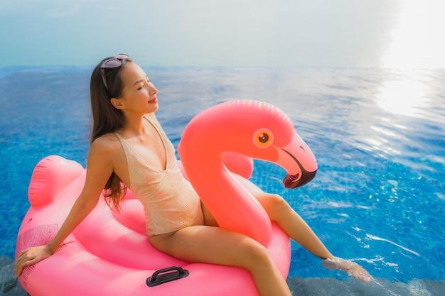Junge asiatische frau des porträts auf aufblasbarem flamingo um swimmingpool im freien im hotelerholungsort