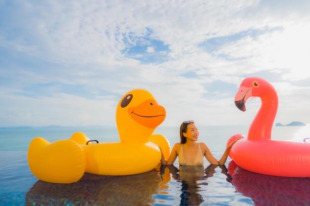 Junge asiatische frau des porträts auf gelber ente des aufblasbaren schwimmers und rosa flamingo um swimmingpool im freien im hotel und im erholungsort