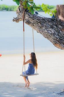 Junge asiatische frau des porträts, die auf schwingenseil und meer um strandseeozean-kokosnusspalme sitzt