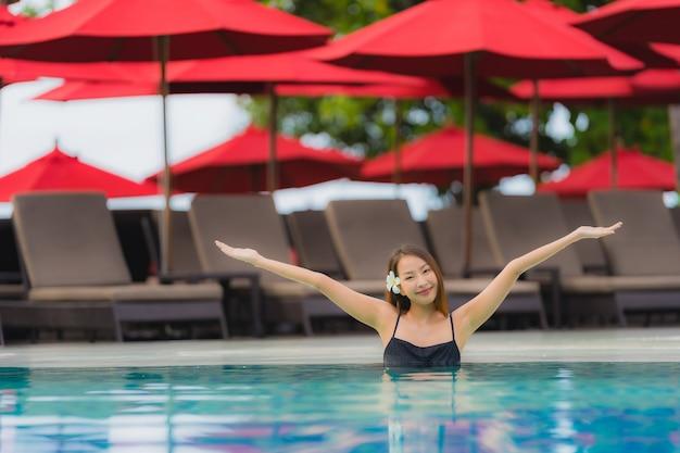 Junge asiatische frau des porträts entspannen sich das lächeln, das um swimmingpool im freien im hotelerholungsort mit seeozeanblick glücklich ist