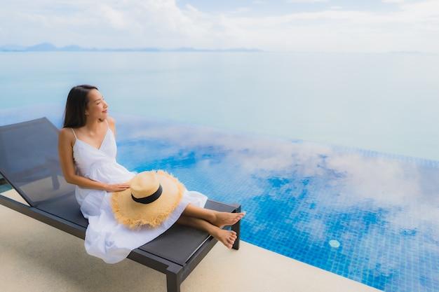 Junge asiatische frau des porträts entspannen sich das lächeln, das um swimmingpool im hotel und im erholungsort glücklich ist