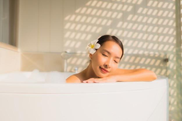 Junge asiatische frau des porträts entspannen sich nehmen ein bad in der badewanne