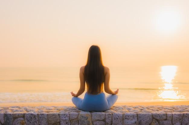 Junge asiatische frau des porträts meditieren um seestrandozean bei sonnenaufgang