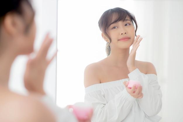 Junge asiatische frau des schönen porträts, die sahnefeuchtigkeitscreme aufträgt
