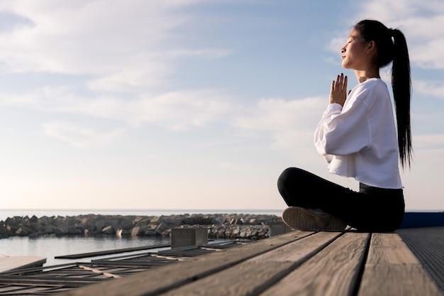 Junge asiatische frau, die am meer meditierend sitzt