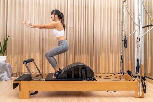 Junge asiatische frau, die an pilates-reformer-maschine während ihres gesundheitstrainingstrainings arbeitet
