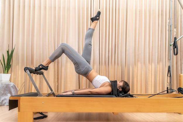 Junge asiatische frau, die an pilates-reformer-maschine während ihres gesundheitsübungstrainings arbeitet