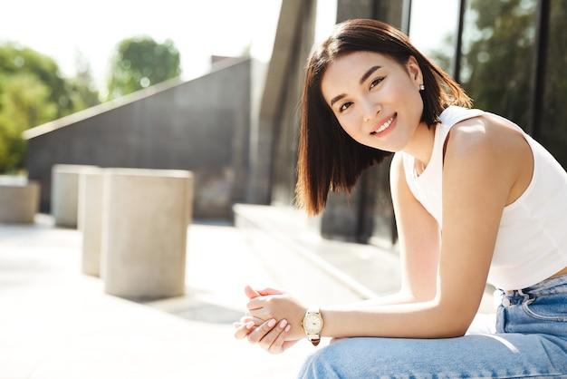 Junge asiatische frau, die auf bank nahe gebäude sitzt und kamera mit glücklichem gesicht lächelt