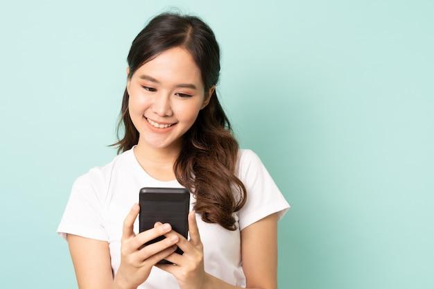 Junge asiatische frau, die auf blauem hintergrund lächelt