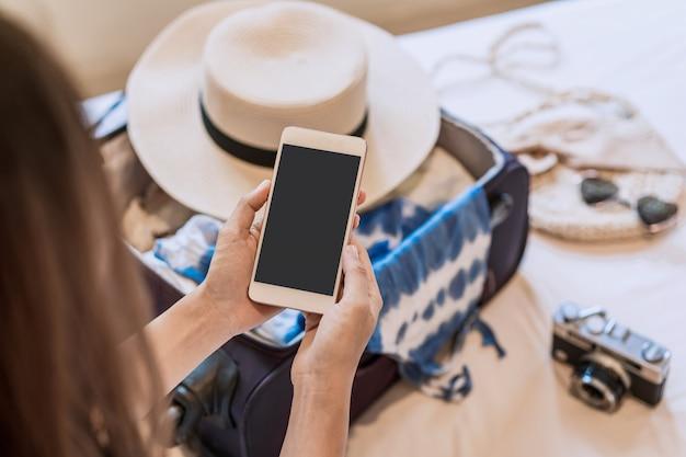 Junge asiatische frau, die auf dem bett unter verwendung des smartphones sitzt und ihren koffer packt, der reise für die sommerferien vorbereitet