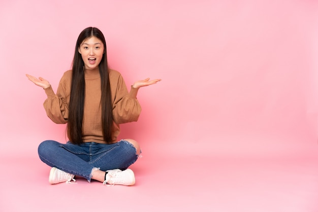 Junge asiatische frau, die auf dem boden auf rosa wand mit schockiertem gesichtsausdruck sitzt