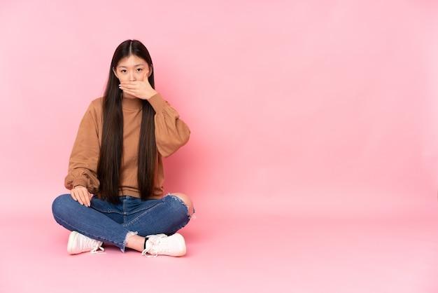 Junge asiatische frau, die auf dem boden sitzt