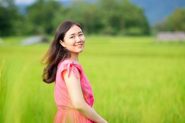 Junge asiatische frau, die auf dem reisgebiet genießt