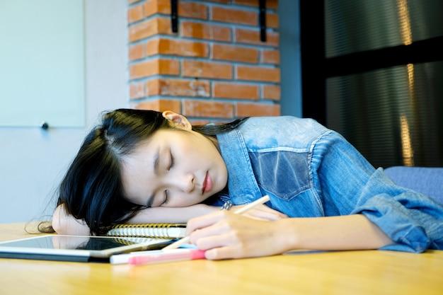 Junge asiatische frau, die auf dem schreibtisch schläft