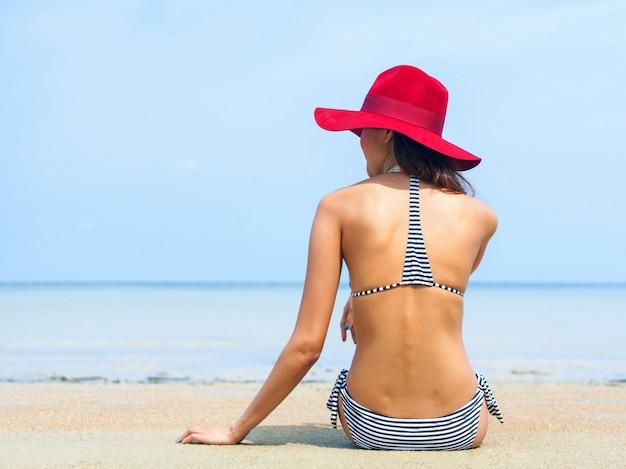 Junge asiatische frau, die auf dem strand sich entspannt.