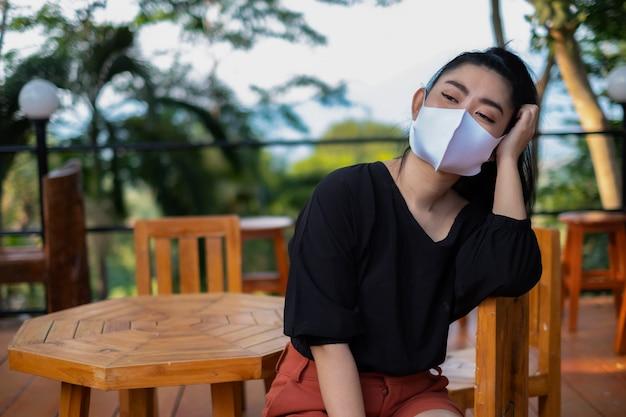Junge asiatische frau, die auf dem stuhlholz sitzt und auf eine gesichtsmaske setzt, um von atemwegserkrankungen in der luft als grippestaub und smog im park, frauen-sicherheitsvirus-infektionskonzept zu schützen