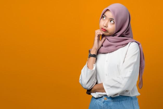 Junge asiatische frau, die auf gelb verwirrt denkt und sich verwirrt fühlt