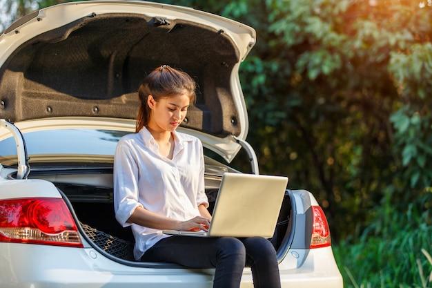Junge asiatische frau, die auf hatchbackauto mit notizbuch sitzt