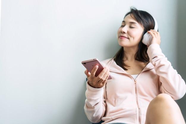 Junge asiatische frau, die auf sofa sitzt und musik hört