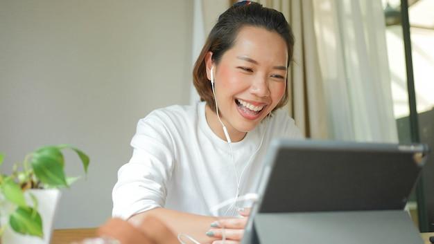 Junge asiatische frau, die auf tisch sitzt und film- oder unterhaltungs-median-digital-tisch anschaut