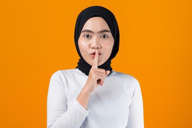 Junge asiatische frau, die bittet, ruhig zu sein